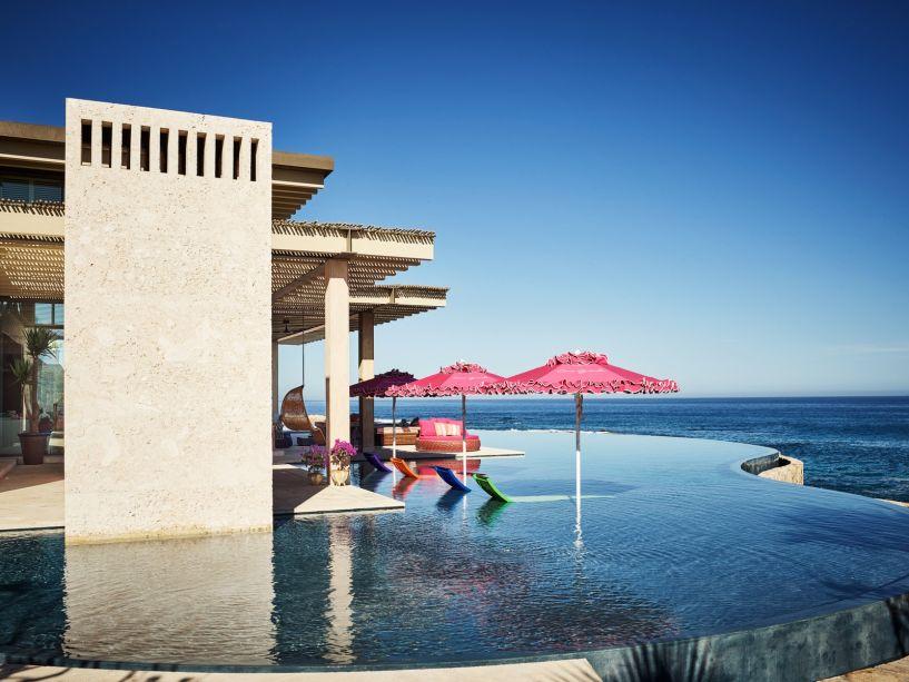 """O designer Ken Fulk e o arquiteto Víctor Legorreta, criaram uma piscina no México em que os limites entre a água e o oceano se misturam. Fulk escreveu na época: """"Quando você olha para o grande espelho d'água do pátio central, uma plataforma hidráulica se eleva com o toque de um botão para acomodar uma mesa de jantar e cadeiras""""."""