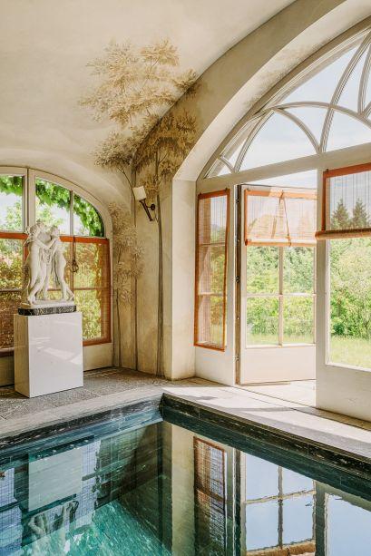 Rodeada por um mural pintado à mão e sombras de bambu, a piscina assinada pelo Studio Peregalli parece uma caixa de jóias. Ela fica em um retiro da Baviera, em uma casa tradicional alemã. Uma escultura do início do século 19, de Antonio Canova, contempla-a da borda.