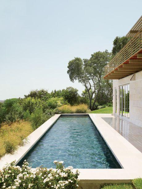 Para criar esta casa na encosta de Austin, o Flato Architects se uniu a Terry Hunziker para construir uma casa minimalista. A piscina olímpica, vista aqui, é cercada por calcário e gramados. Não muito longe fica um gramado, um terraço com sombra de pérgola e um punhado de carvalhos.