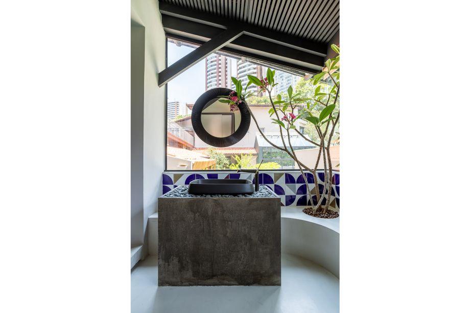 O banheiro emoldura um belo jardim que ganha vida ao fundo. Nele, o concreto é usado para dar suporte à cuba. O destaque aqui, porém, fica para os ladrilhos hidráulicos azuis, que também fazem referência ao modernismo brasileiro e à nomes como Athos Bulcão.
