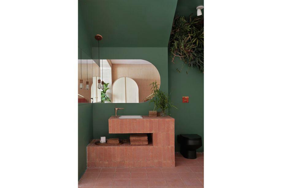 Estúdio Hygge - Melina Romano. CASACOR São Paulo 2019. A cor verde dá o tom no banheiro deste estúdio de 68m², fazendo contraste à cerâmica terracota. Integrado com o quarto de forma aberta, o espaço recebeu uma intervenção com vegetação tropical feita pela florista Aline Matsumoto.