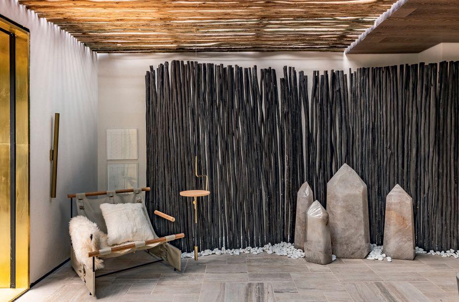 CASACOR São Paulo. Casa Moysés - Triart Arquitetura. O protagonista é a biriba, uma madeira retorcida. Ela aparece no biombo e compõe os painéis que dividem os espaços. As formas irregulares da madeira dão textura e uma linearidade rústica para o espaço, que ainda conta com cristais na decoração.