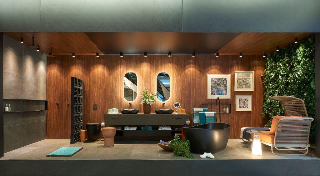 Sala de banho com duas pias, dois espelhos elípticos, uma banheira preta, sofá e jardim vertical