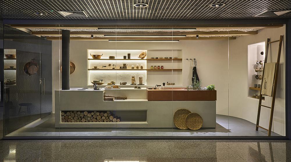 Vista externa da cozinha, com bancada e estante com utensílios ao fundo