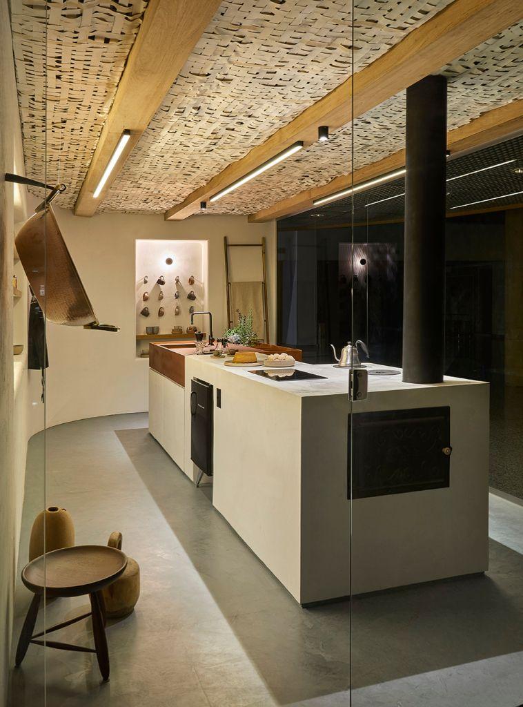 Vista externa da cozinha, com bancada e arranjo de canecas ao fundo