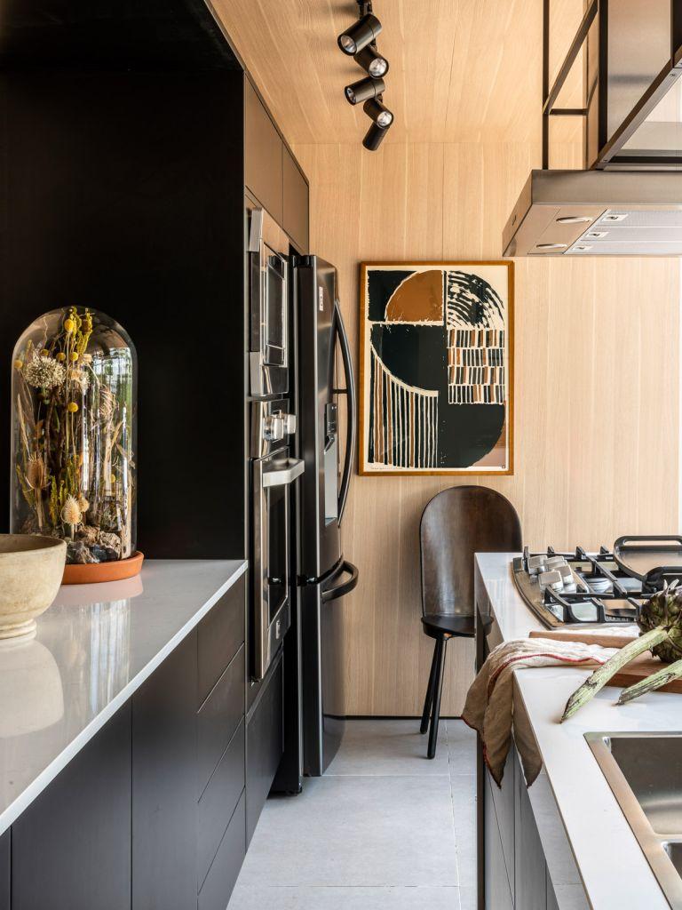 Detalhe da cozinha Tempero da vida com bancada, geladeira e parede com quadro ao fundo