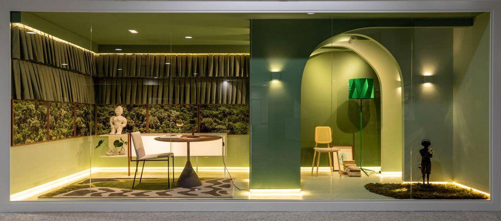 Visão frontal do contêiner composto por home office e pequeno estar, predomina a cor verde