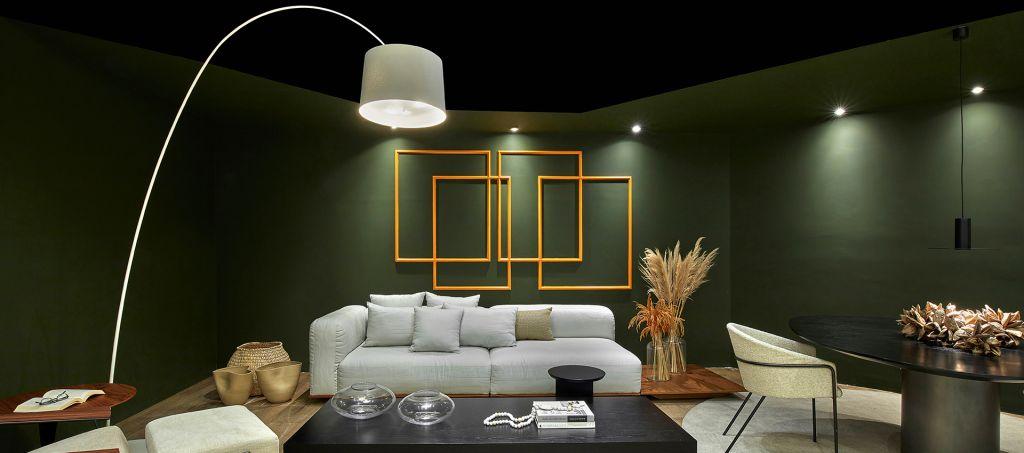 Living com paredes verdes e obras geométricas amarelas. Sofá branco e mesa de centro preta