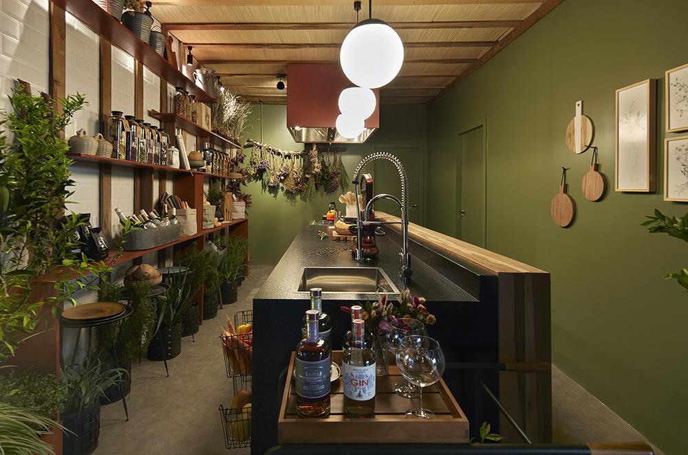 Cozinha com bancada, pendentes esféricos e muitas plantas