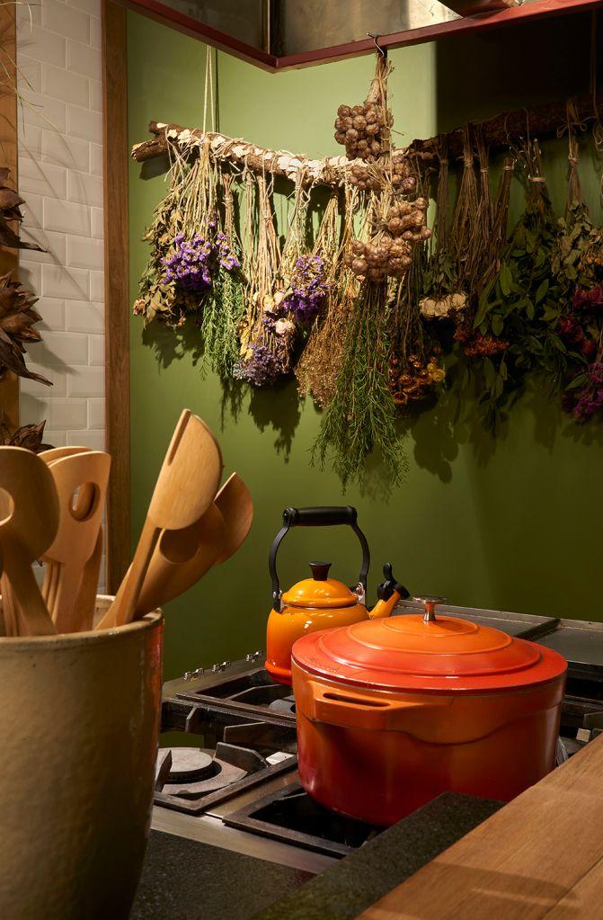 Detalhe com panelas e arranjo com temperos e flores na parede