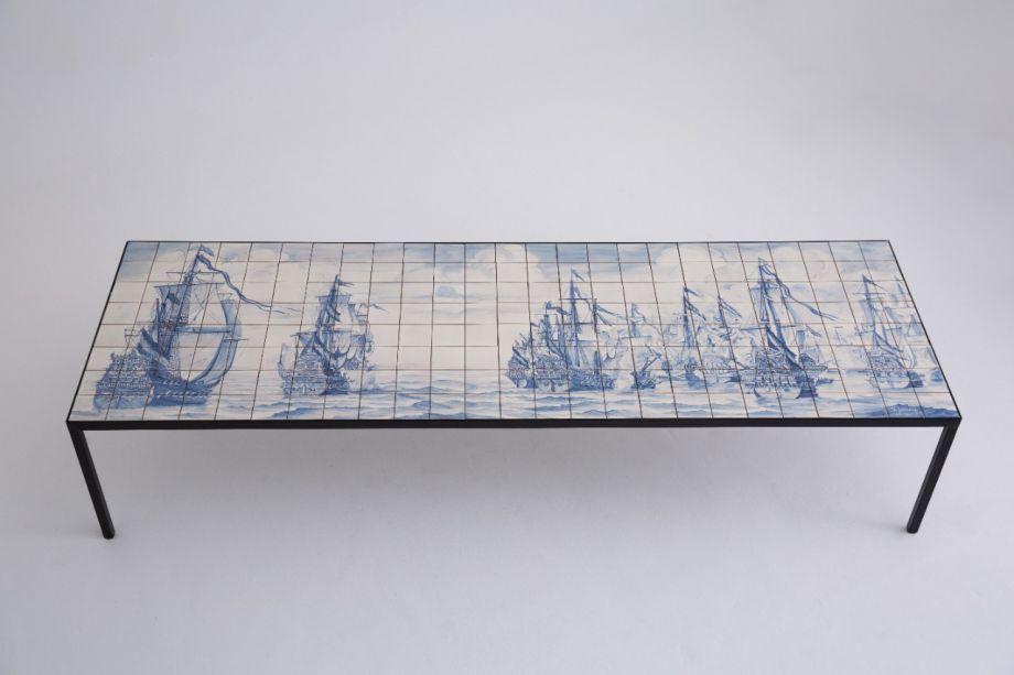 Entre os lançamentos está a mesa portuguesa de Marcio Kogan – uma peça complexa de ser executada, tanto por sua extensão quanto por sua estrutura, que leva quatro pés muitos finos em suas extremidades. Nela, o tampo foi produzido a partir de azulejos pintados à mão por um artesão português.