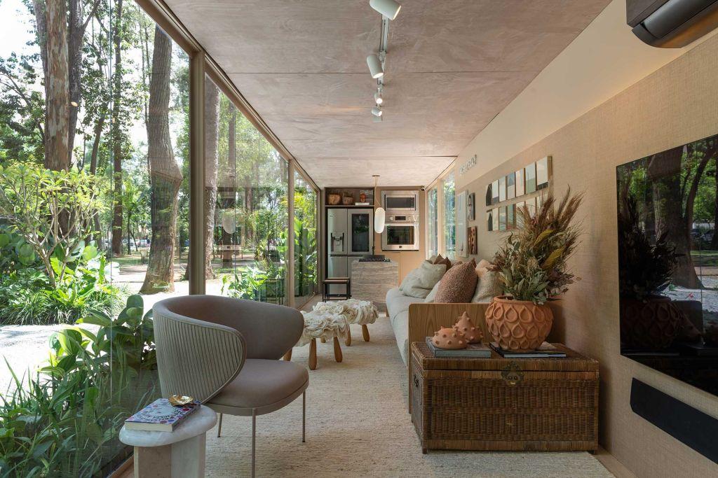 Ambiente integrado composto por living e cozinha. TV e poltrona no primeiro plano e, ao fundo, a cozinha com geladeira, bancada e forno