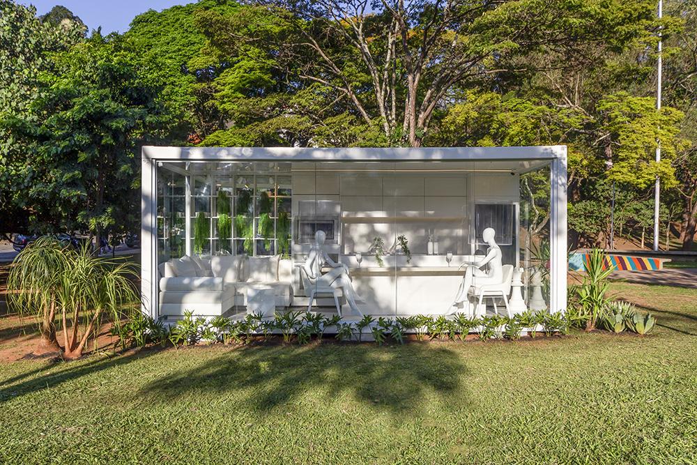 Vista externa do contêiner com gramado e árvores ao fundo. Living branco com mesa e manequins.