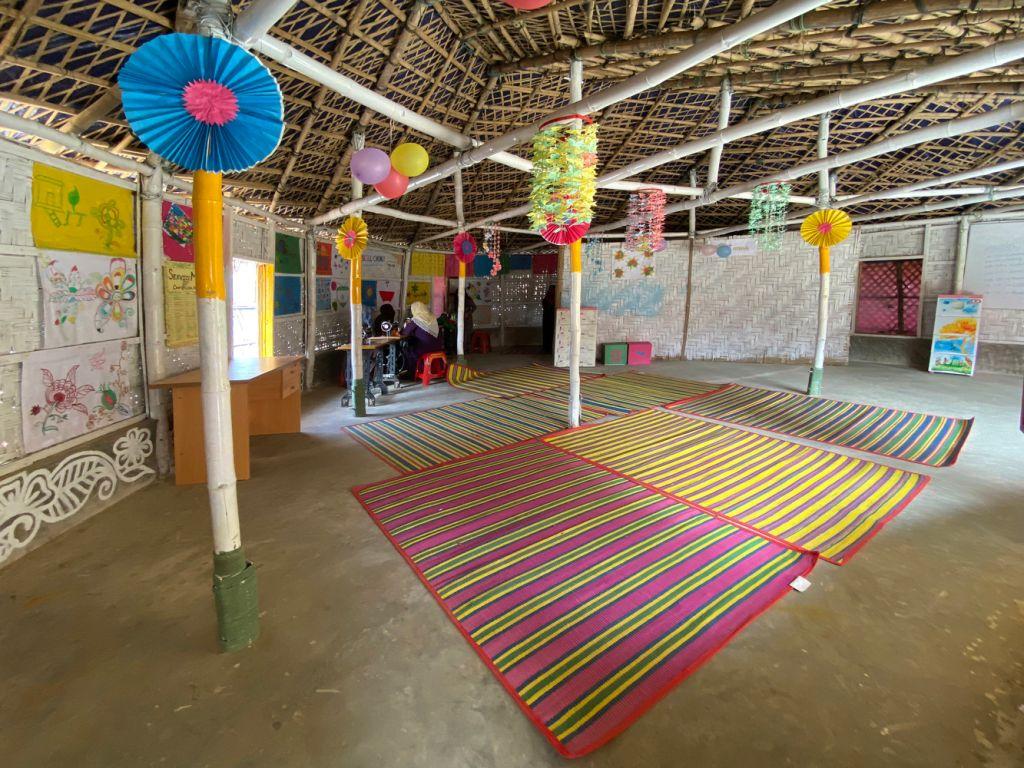 Vista de uma das salas centro comunitário com enfeites coloridos pendurados e desenhos nas paredes