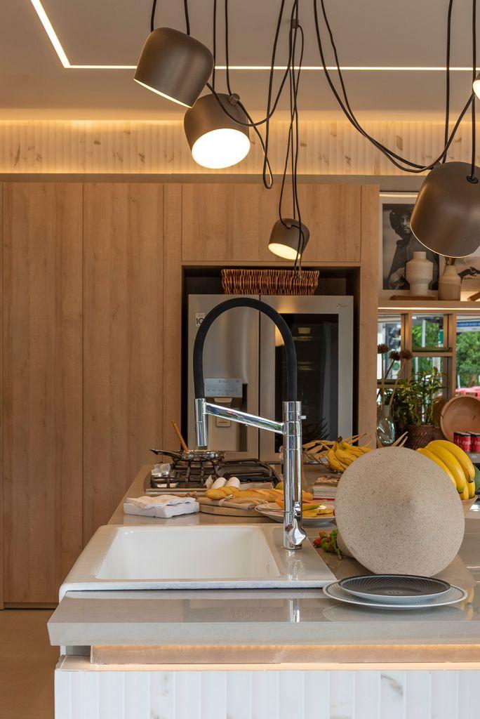Bancada da cozinha com pia, algumas frutas e luminária acima