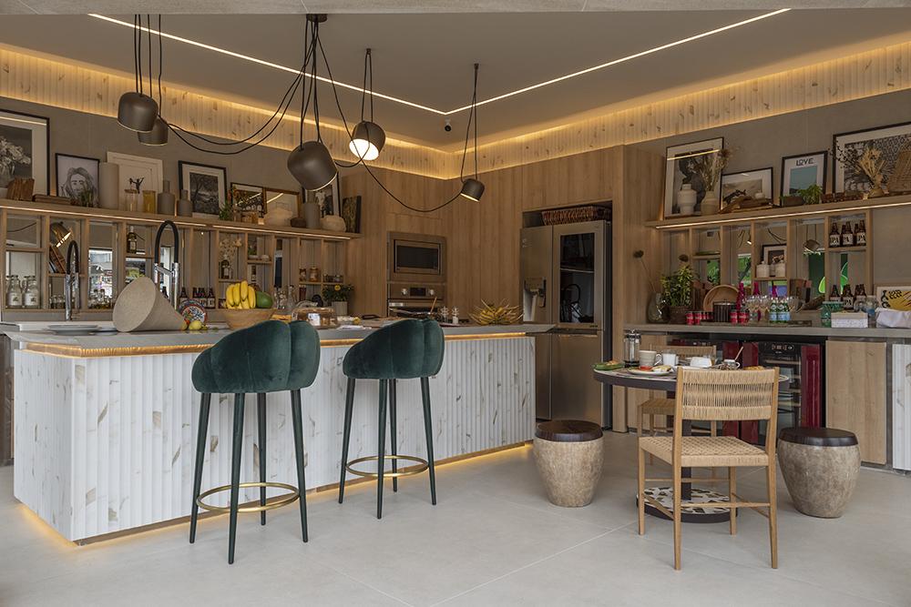 Cozinha com ilha, dois bancos altos com assento verde escuro em veludo e mesa pequena com duas cadeiras