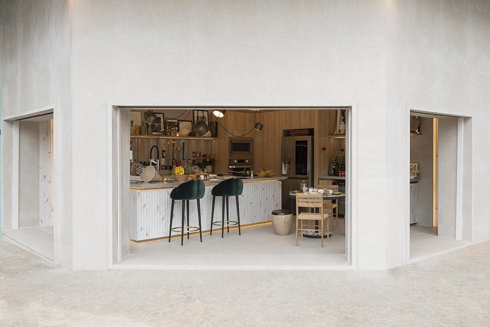 vista externa da cozinha com bancada, mesa, cadeiras e dois bancos altos
