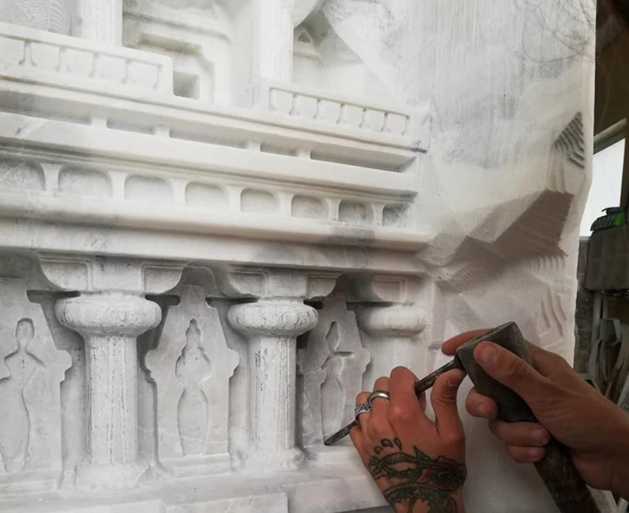 Mãos de artesão esculpindo mesa em mármore branco