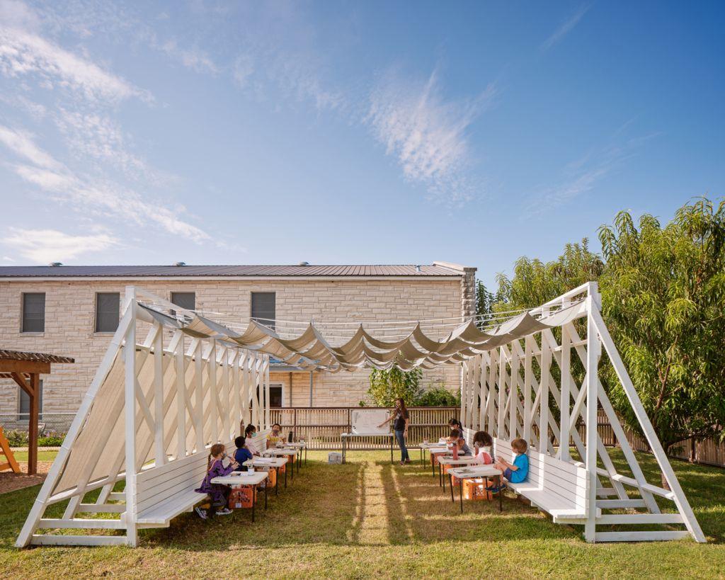 Vista frontal da sala de aula provisória ao ar livre em formato de tenda com crianças tendo aula