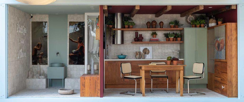Vista frontal do Espaço Sagrado composto por lavatório e cozinha com bancada ao fundo, mesa de madeira e duas cadeiras