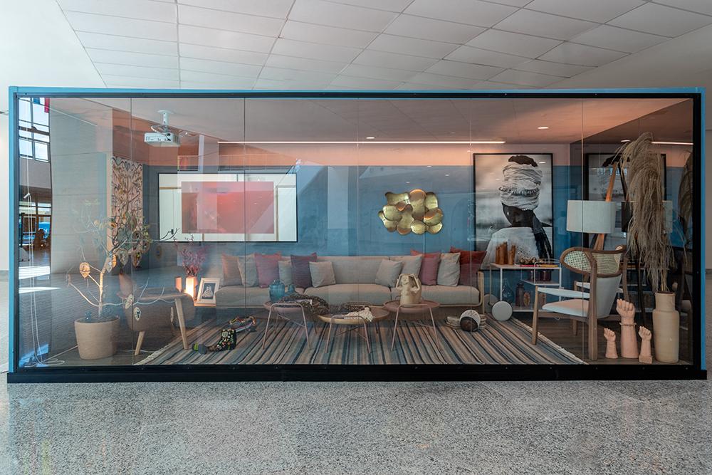 Imagem frontal do contêiner com sofá, telão, mesas de centro e, ao fundo, fotografia e escultura dourada
