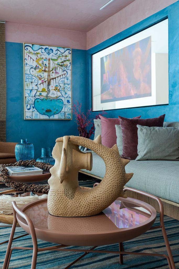 Foto vertical com escultura em primeiro plano, sofá e telão em segundo