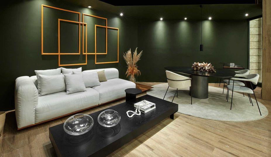 Estar Conviver - Marina Diniz. O projeto propõe a integração do estar e jantar aliando conforto e design na medida. No estar, um amplo sofá em linho, material também da poltrona e do pufe Zanini de Zanine, todos contrapostos ao tom verde Montanha Infinita, da Coral, nas paredes.