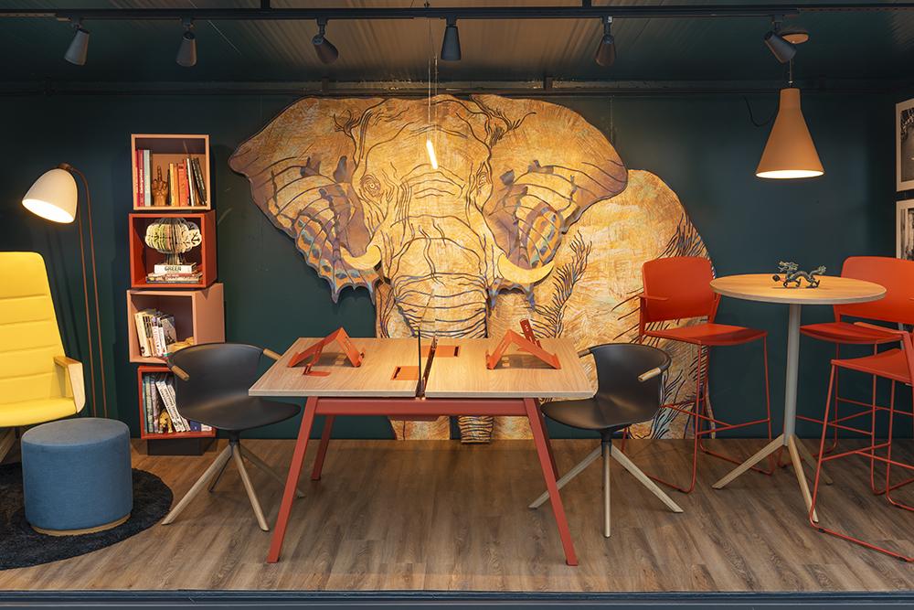 Vista frontal do co-working com mesa, duas cadeiras, uma estante à esquerda e na parede do centro um elefante grafitado