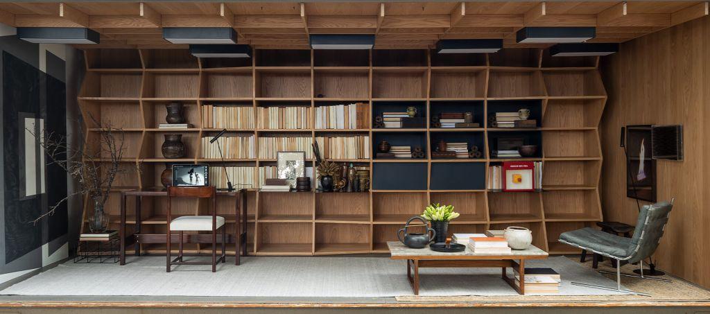 home office e biblioteca com estante em zigue-zague em madeira. Poltrona no canto direito, mesa com cadeira no esquerdo. Mesa de centro baixa
