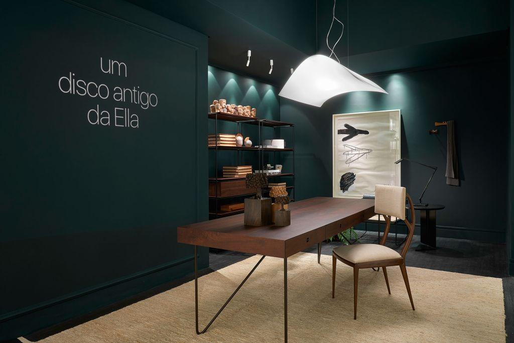 """Home office com mesa em madeira e parede verde escura com um letreiro """"um disco antigo da Ella"""""""