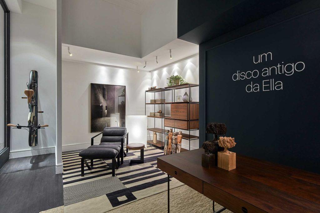 """Home office com mesa em madeira e parede verde escura com um letreiro """"um disco antigo da Ella"""". Bicicleta pendurada na direita"""