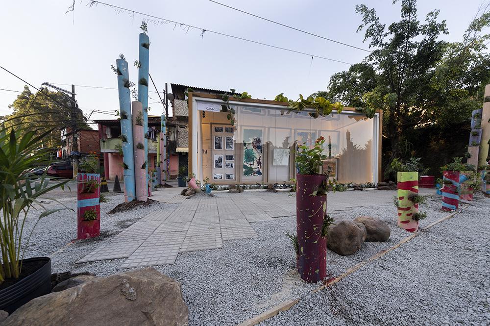 Vista externa da Galeria. Totens coloridos com plantas. Contêiner com obras de arte expostas no centro