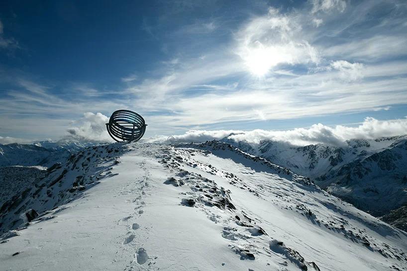 Montanha com neve e céu azul. No topo, estrutura artística