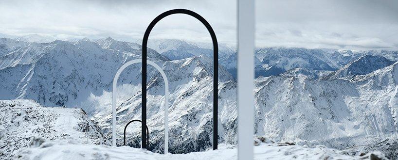 Portais em forma de arco brancos e pretos enfileirados em montanha com neve