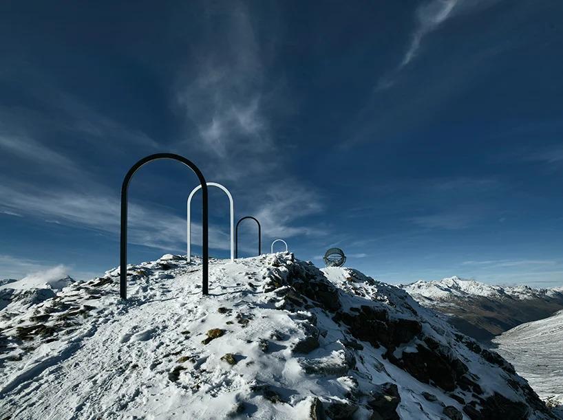 Portais em forma de arco brancos e pretos levando até estrutura artística no topo da montanha