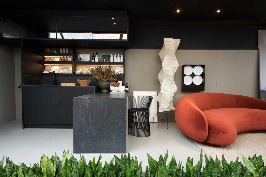 Cozinha do projeto Pra Que Mais, de João Armentano. Foco na bancada preta e sofá vermelho à direita
