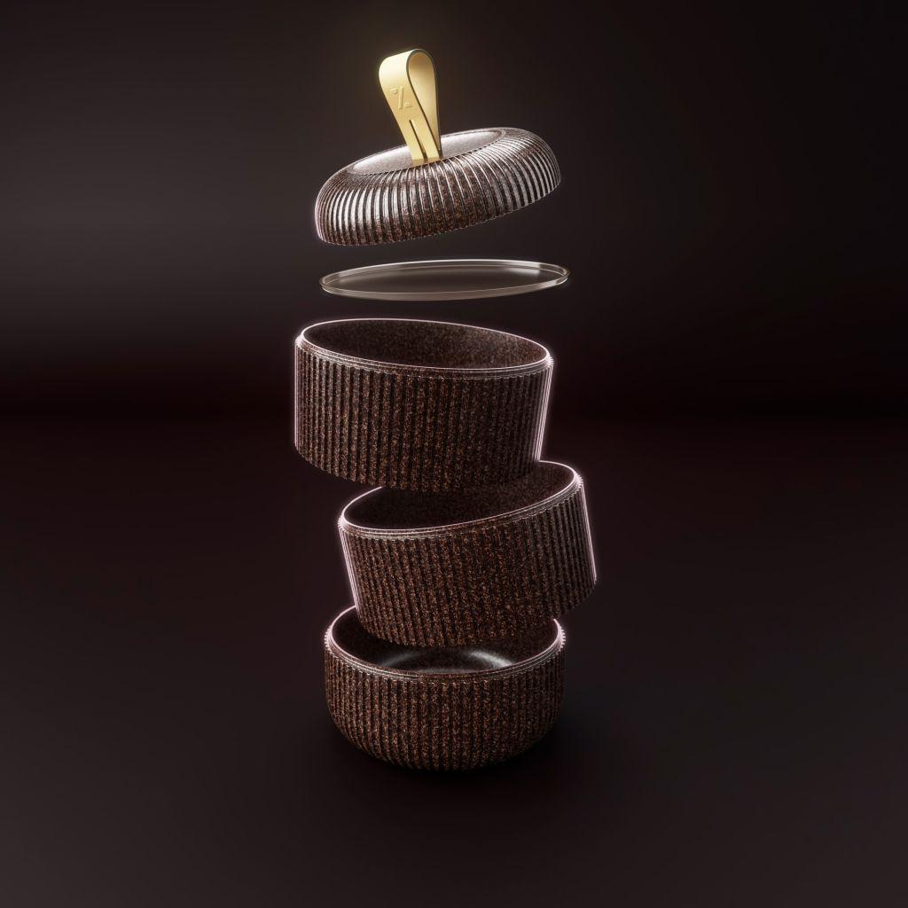 Três potes marrons na vertical levemente desalinhados, um acima do outro com a tampa na cor marrom.