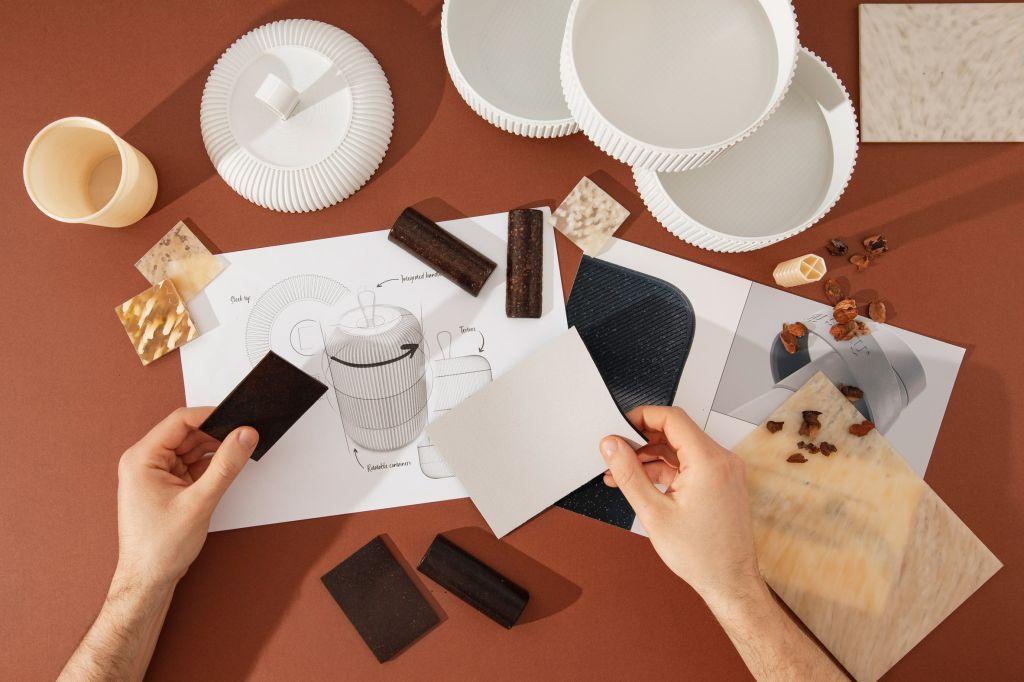 Mesa vista de cima com papeis e amostras de cor, três potes branco abertos e duas mãos segurando amostras de cor.