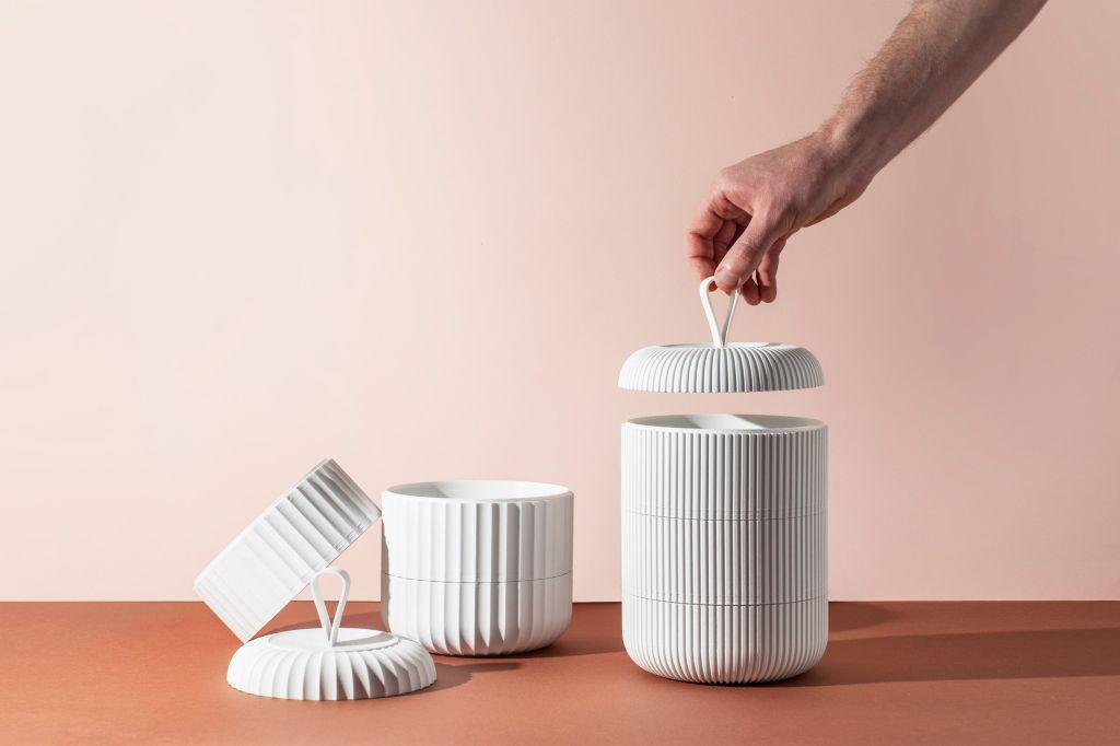 Três potes vazios, um sendo tampado, na cor branca da embalagem reciclável criada pela PriestmanGoode