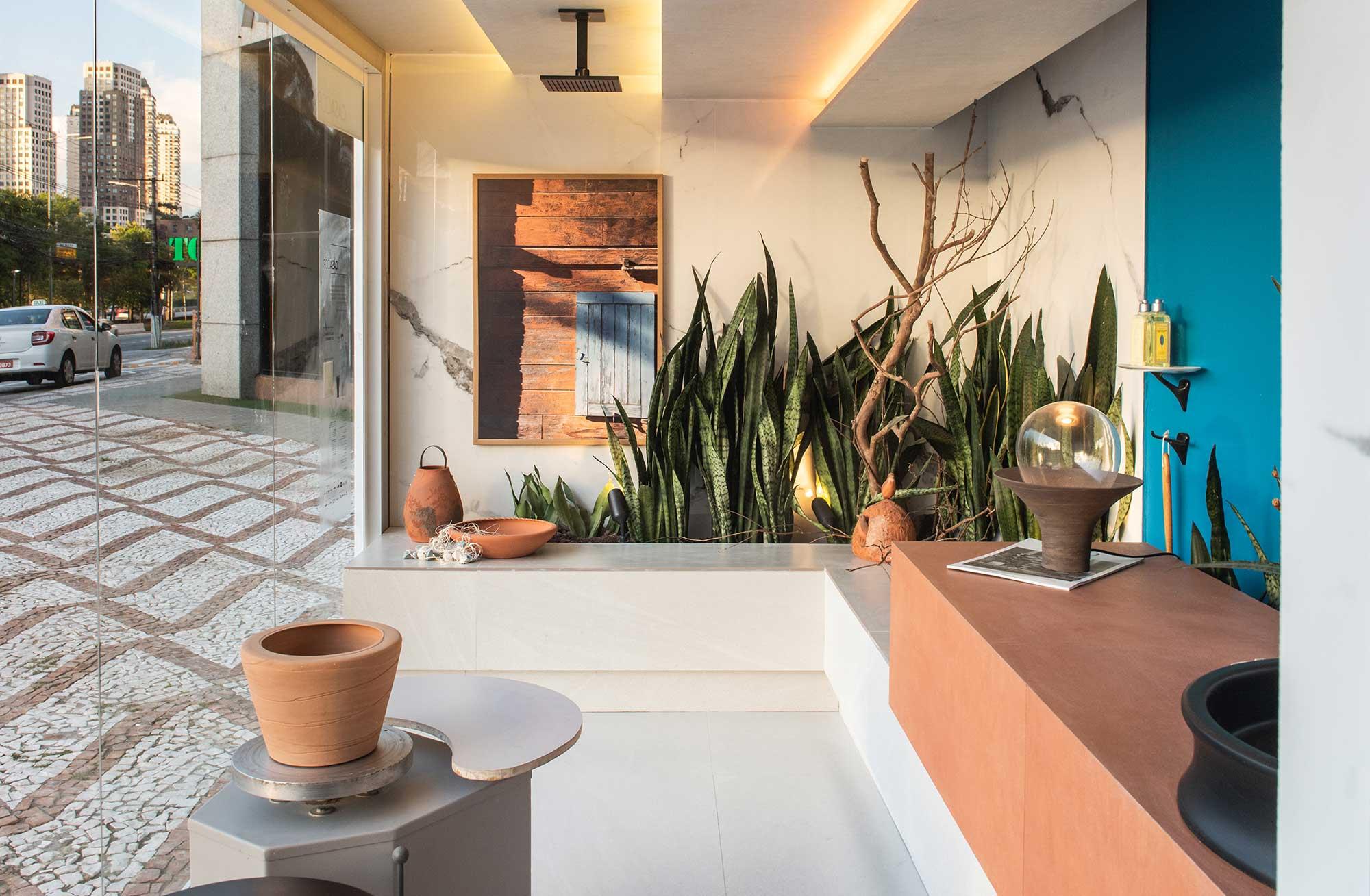 Marcelo Diniz e Mateus Finzetto criaram um jardim dentro do seu Banheiro do Ceramista: a espada-de-São-Jorge aparece junto com galhos secos e uma casinha de João-de-barro.