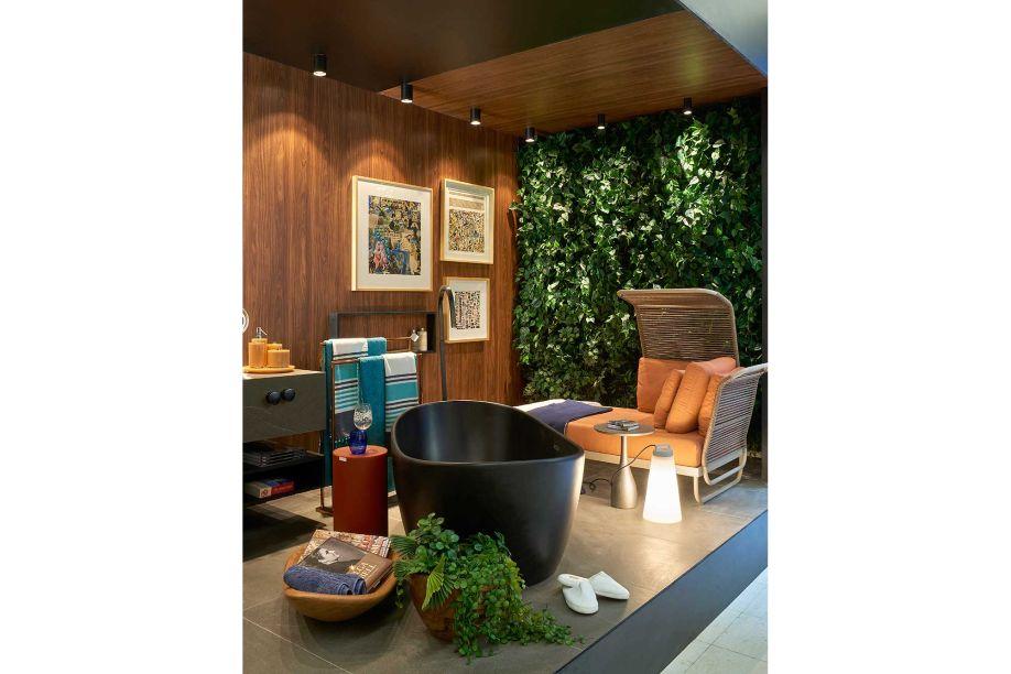 Sala de Banho - Espaço Deca - Ana Paula Paolinelli. Ao fazer uma associação do banheiro a um living externo, a ideia é trazer esse espaço tão íntimo para um uso mais contemplativo e abrangente. A delicada parede verde, com plantas em diferentes nuances, reforça a tendência da arquitetura biofílica.