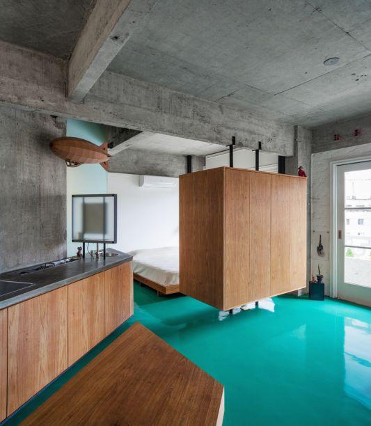 Apartamento Viadutos- Vão Arquitetura. O armário de madeira não só separa em dois ambientes, mas também cumpre sua função original.