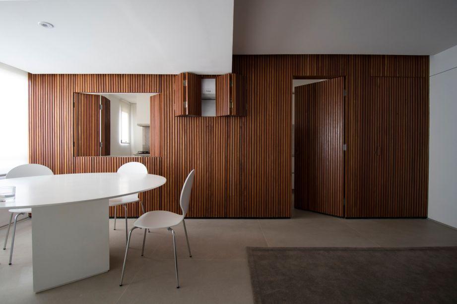 Apartamento ED- Daher Jardim Arquitetura. O painel de madeira, quando aberto, vira portas e janelas, mas quando fechado, uma linda decoração.