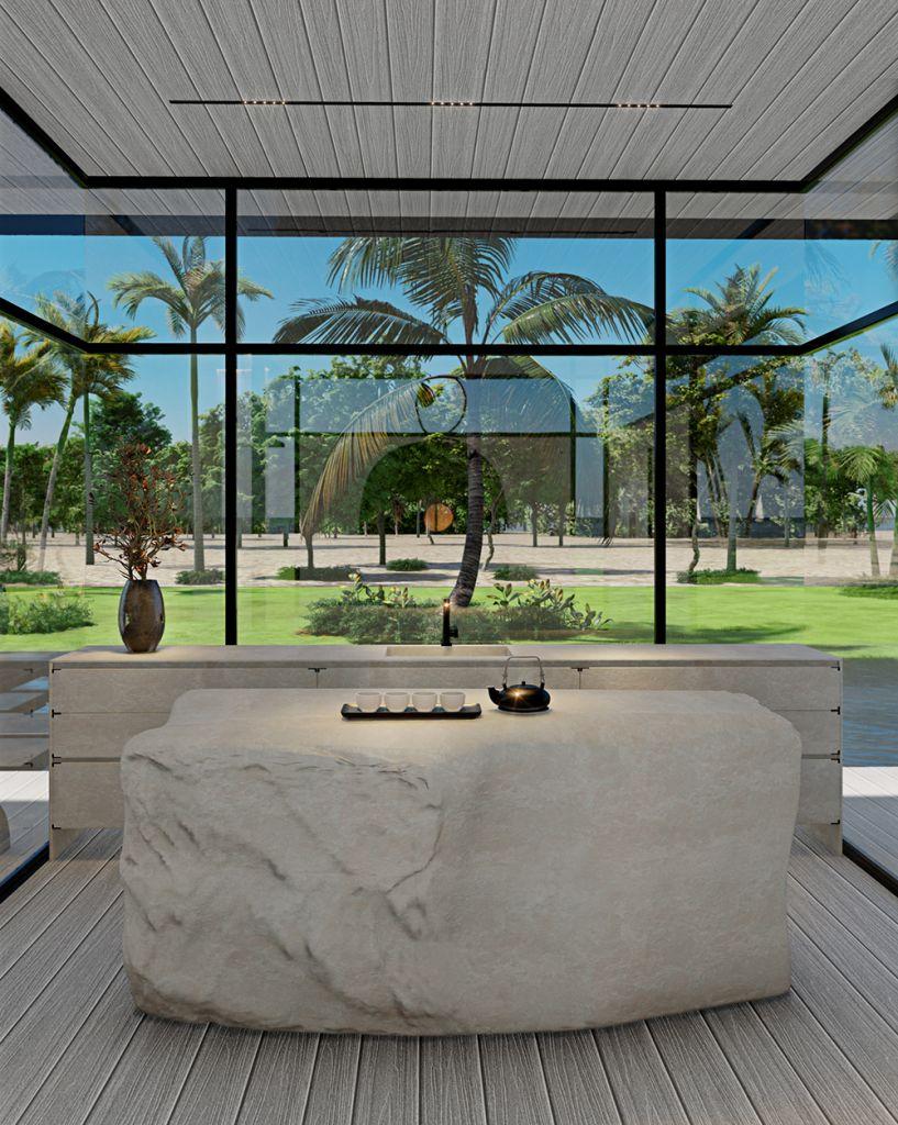 Sala com bancada e mesa central com bule de chá. Grande janela ao fundo