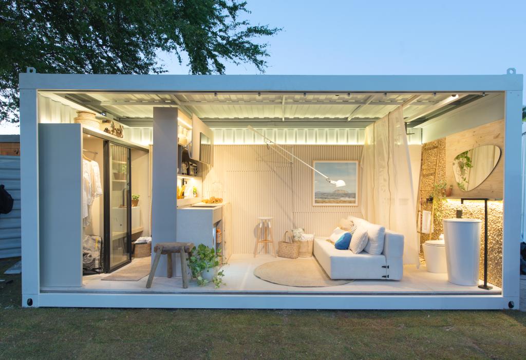 Sala de estar com móveis brancos e peças multifuncionais.