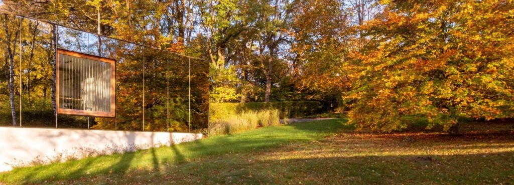 Fachada espelhada refletindo bosque com folhas de outono