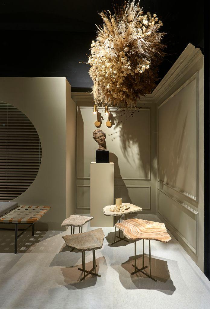 mesas de mármore em formatos irregulares, uma cabeça esculpida sobre um totem e pendente, flores brancas.