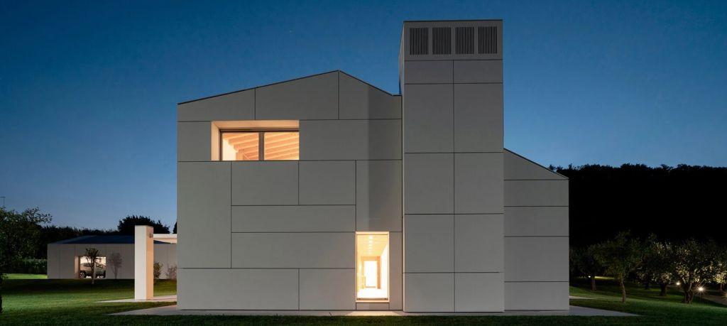 Vista lateral da casa durante a noite com porta e janela no canto superior esquerdo iluminadas