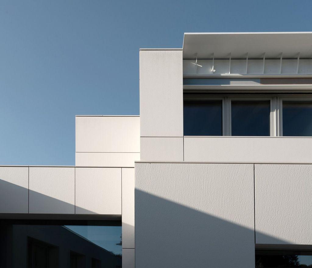 Detalhe do andar superior com os revestimentos e janelas compondo um jogo de luz e sombra