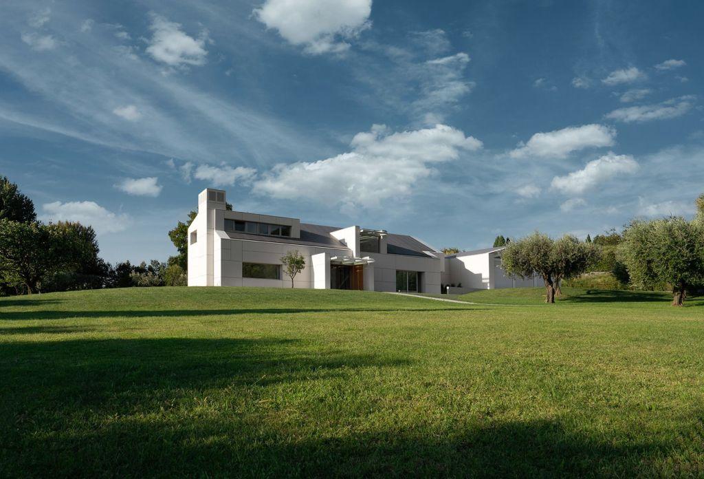Casa vista à distância, com céu azul e grama